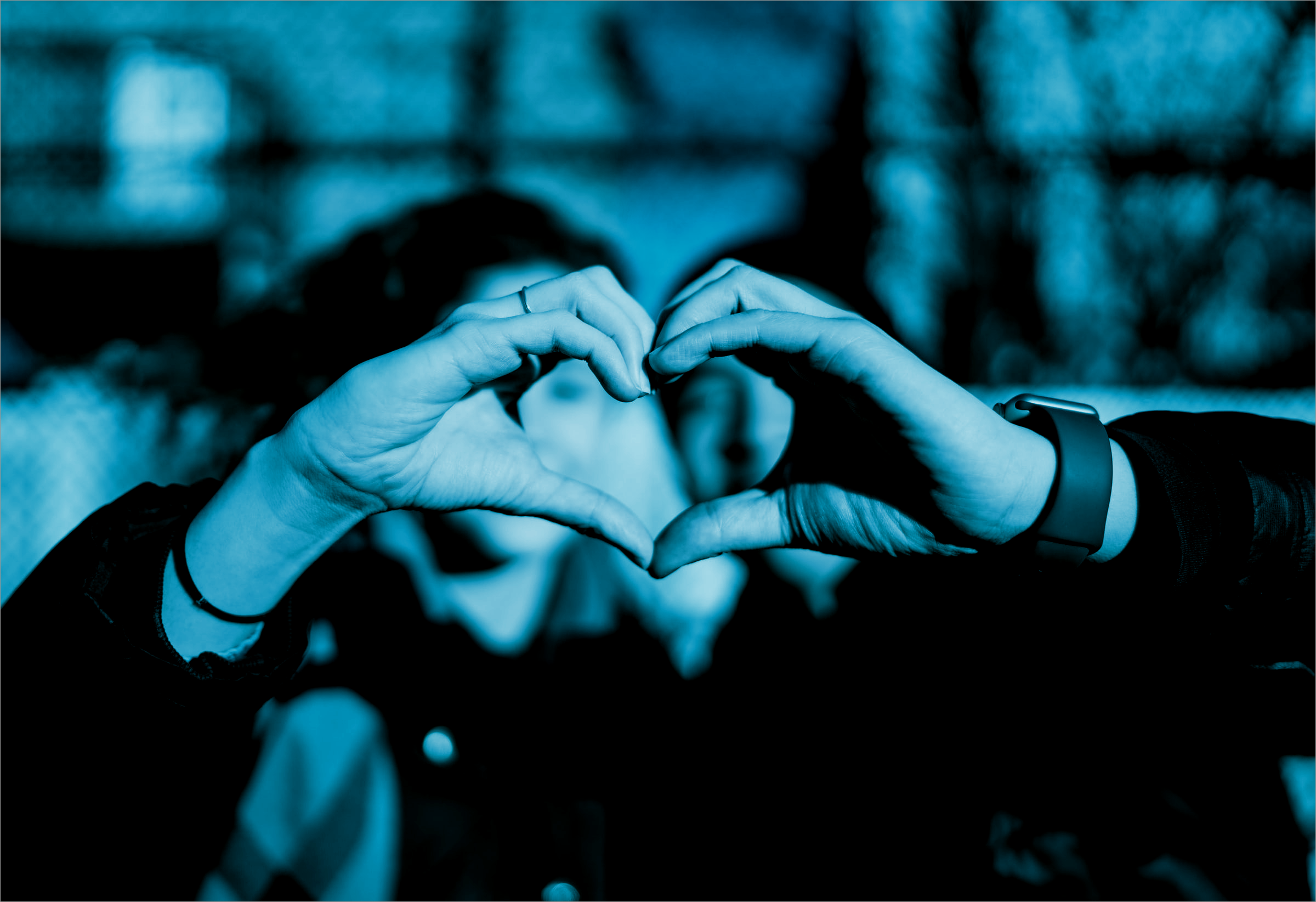 two people forming a heart with their hands
